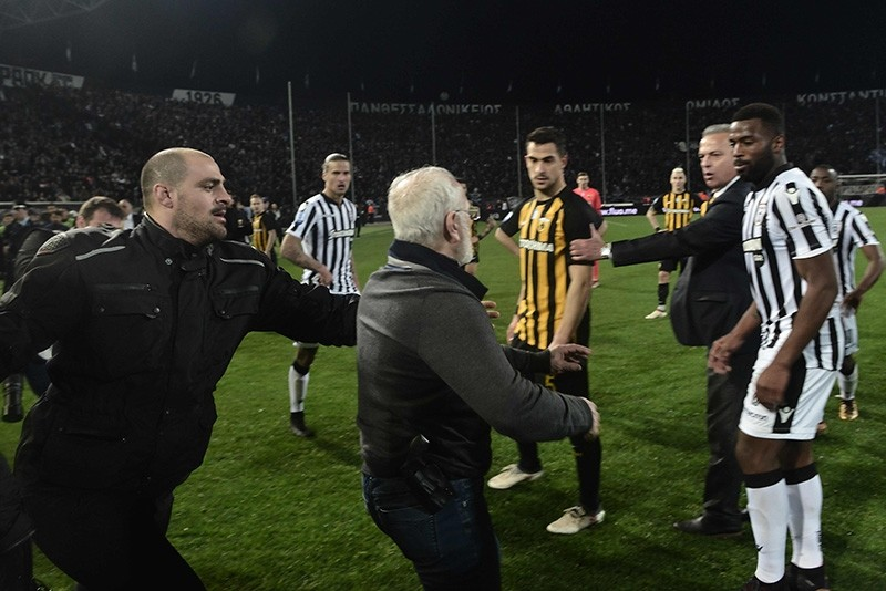 Paok president Ivan Savvidis (C) takes to the pitch carrying a handgun in his waistband (below C), after the referee refused a last minute goal  (AFP Photo)