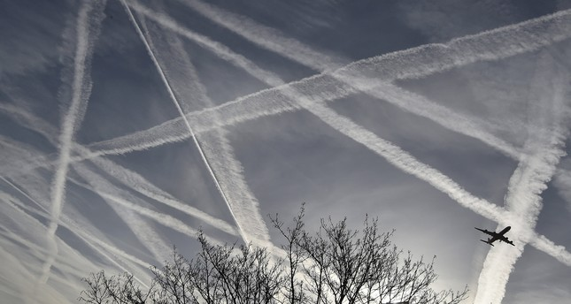 A passenger plane flies through aircraft contrails in the skies near Heathrow Airport in west London, April 12, 2015. (Reuters Photo)