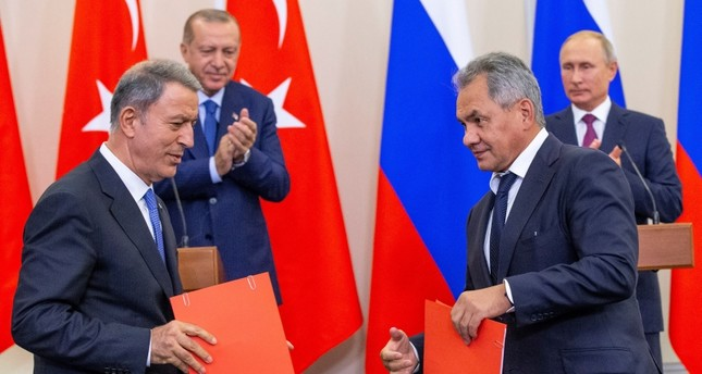 Russian Defense Minister Sergei Shoig (foreground R) and Defense Minister Hulusi Akar shake hands as Russian President Putin (R)  and President Erdoğan (2-L) look on during their joint news conference on Sept 17. (EPA Photo)