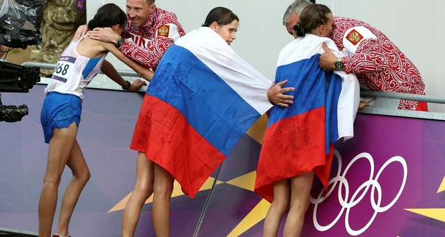 Russia coach Alexey Melnikov congratulates Olga Kaniskina, right, and Russia men's gold medalist Sergey Kirdyapkin congratulates Anisya Kirdyapkina, left, at the 2012 Summer Olympics in London. (AP Photo)