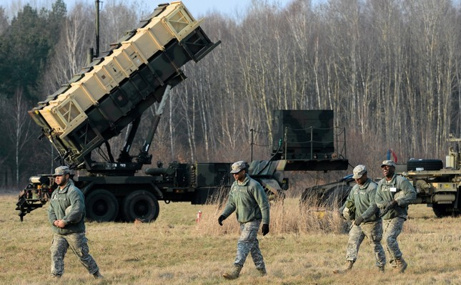 U.S soldiers walk next to  a Patriot missile defense battery during join exercises at the military grounds in Warsaw, March 21, 2015.