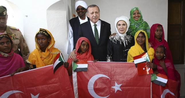 President Erdoğan (C), accompanied by first lady Emine Erdoğan, pose for a photograph with Sudan's President Omar al-Bashir and first lady Widad Babiker Ömer Modawi alongside local people holding the Sudanese and Turkish flags in Port Sudan, Dec. 25,