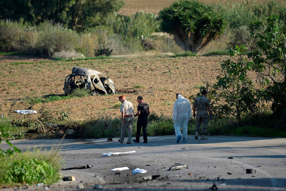 Police and forensic experts inspect the wreckage of a car bomb believed to have killed journalist and blogger Daphne Caruana Galizia close to her home in Bidnija, Malta, Oct. 16, 2017. (AFP Photo)