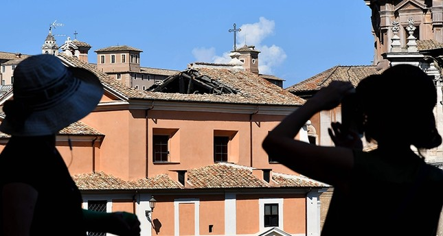 People take photos of the San Giuseppe dei Falegnami Church after its roof collapsed at the Roman forum in Rome, on Aug. 30, 2018. (AFP Photo)