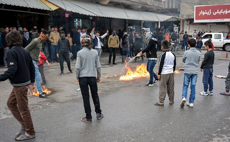 A picture taken on December 20, 2017 shows a protester pouring oil on a fire in a street during a demonstration against political corruption in the city of Rania, in northern Iraq. (AFP Photo)