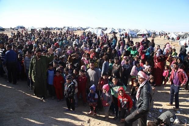 Syrian refugees stuck at the Jordanian-Syrian border wait to cross into the Hadalat area of Jordan.