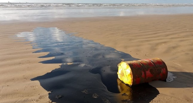 Handout picture released by the Sergipe State Environment Administration (Ademas) on Sept. 27, 2019, showing a barrel of oil spilled on a beach in Barra dos Coqueiros municipality, Sergipe state, Brazil. (AFP)