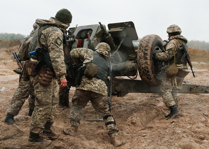 Ukrainian servicemen prepare a 122-mm towed howitzer D-30  to fire during a military exercise on the Devichki shooting range, about 85 km of capital Kiev, Ukraine, 26 October 2017 (EPA Photo)