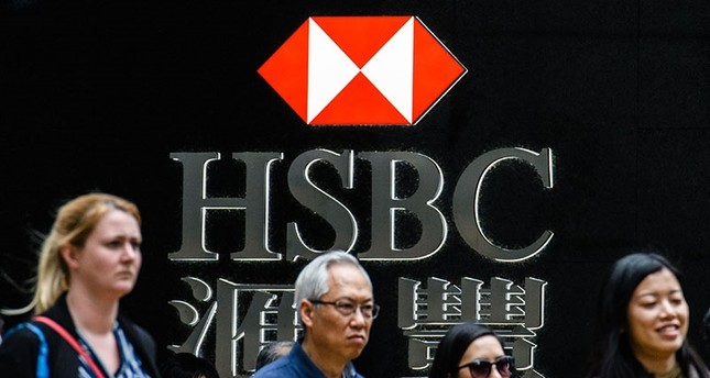 Pedestrians stand outside a branch of HSBC bank in Hong Kong on Feb. 20, 2018. (AFP Photo)