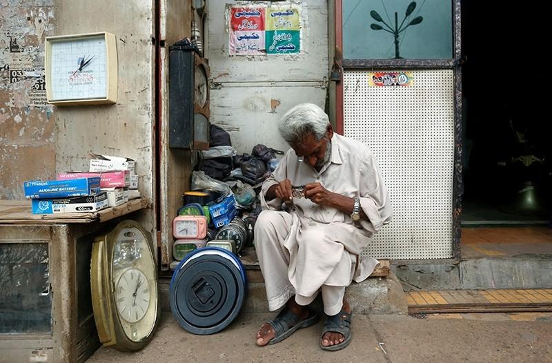 An elderly man checks a wristwatch while repairing it at his makeshift stall along a sidewalk in Karachi, Pakistan July 29, 2017 (Reuters Photo)