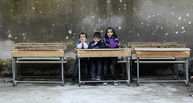 Children sit on school benches at Al-Tawheed school in Aleppo in this January 1, 2013 file photograph. (Reuters Photo)