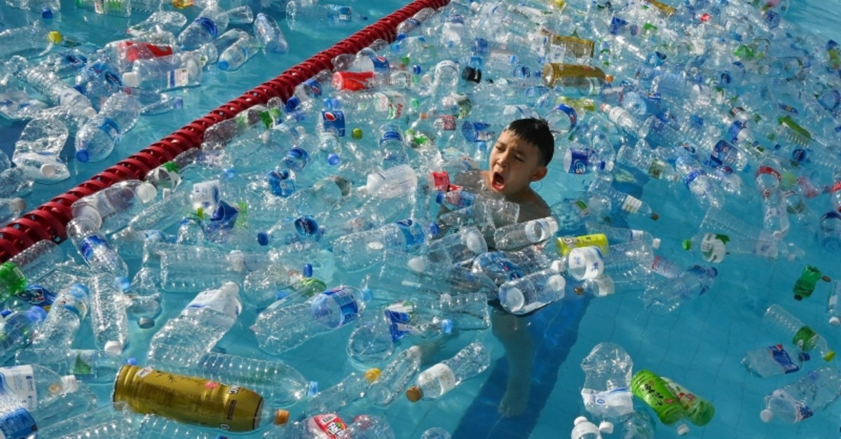 A child swims in a pool filled with plastic bottles during an awareness campaign to mark the World Oceans Day in Bangkok on June 8, 2019. (AFP Photo)