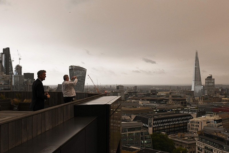Office workers stand on their balcony to photograph the darkened sky over London on October 16, 2017 caused by warm air and dust swept up by storm Ophelia.
