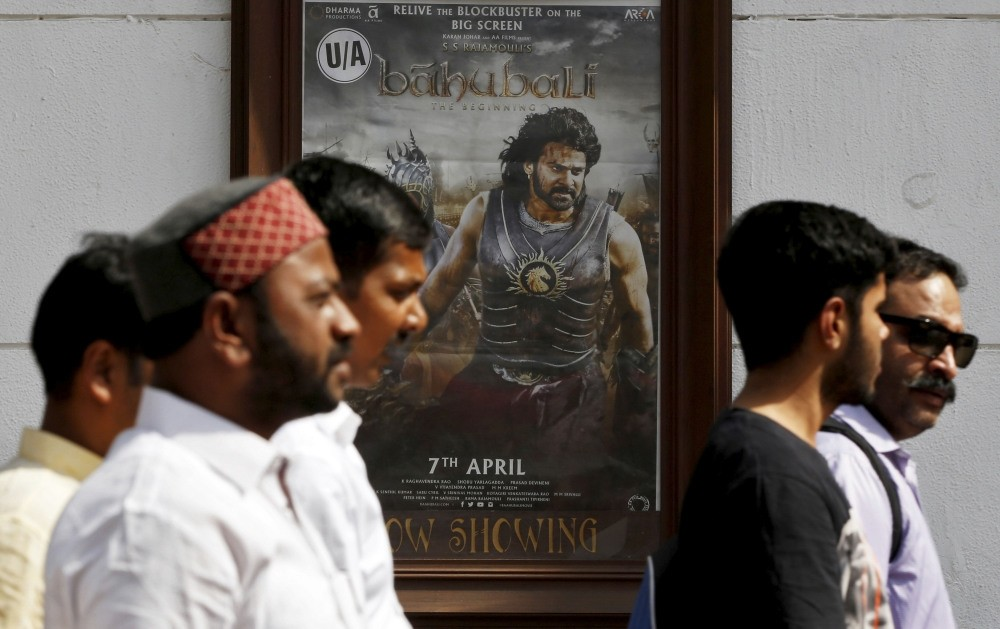 People walk past a poster of the Indian movie u201cBaahubali: The Beginningu201d outside a movie theater in New Delhi. (Reuters Photo)