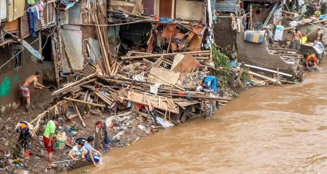 Indonesians clean their homes and cutlery along the river in Jakarta on Jan. 3, 2020, after flooding triggered by heavy rain that started on New Year's Eve hit the area. Photo by BAY ISMOYO / AFP