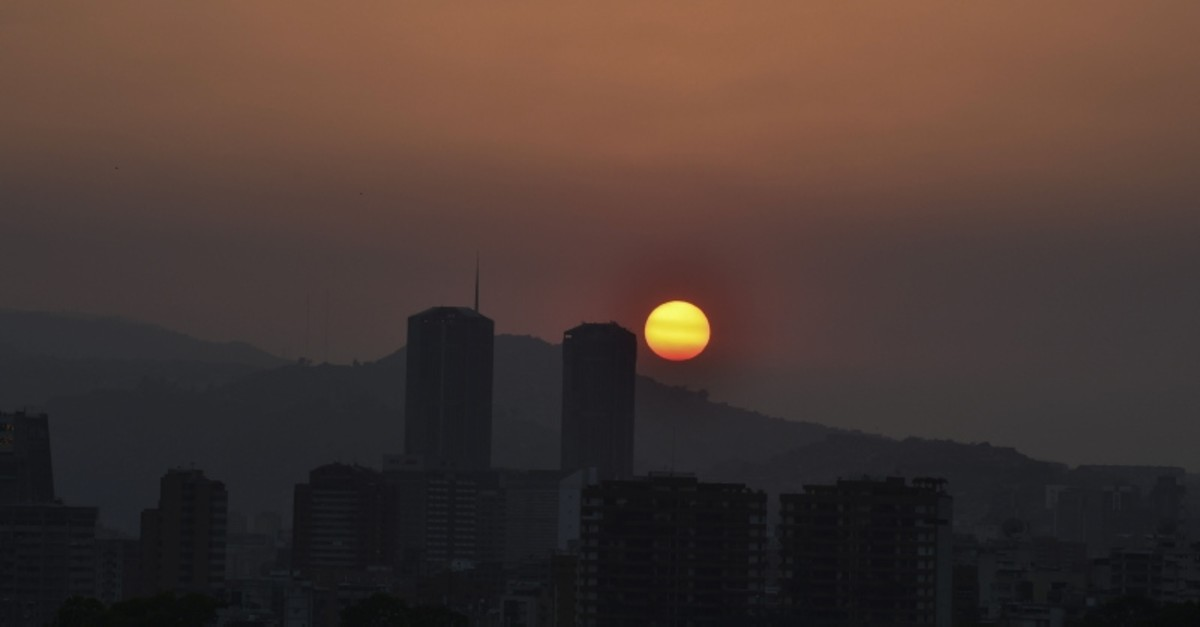 The sun sets in Caracas during a partial power cut on March 25, 2019. (AFP Photo)