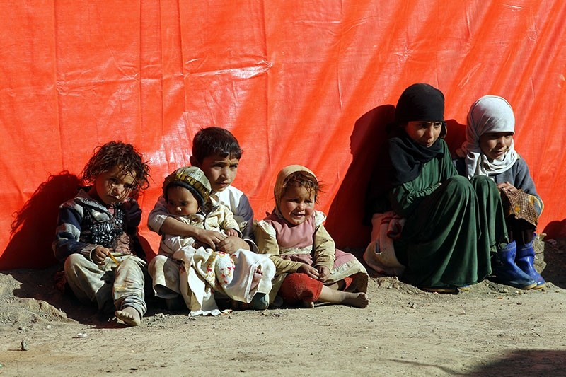 Displaced Yemeni children sit outside a makeshift shelter exposing themselves to the sun light to try and keep them warm at a camp for Internally Displaced Persons (IDPs) in the northern province of Amran, Yemen, Jan. 10 2018. (EPA Photo)