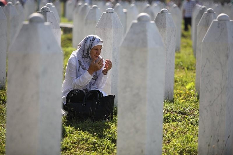 An elderly woman prays between gravestones on the Potocari Memorial Center in Srebrenica, Bosnia and Herzegovina, 11 July 2017. (EPA Photo)