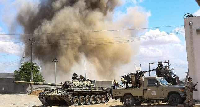 This picture taken on April 12, 2019 shows a smoke plume rising from an air strike behind a tank belonging to forces loyal to Libya's Government of National Accord (GNA), during clashes near Tripoli. (AFP Photo)