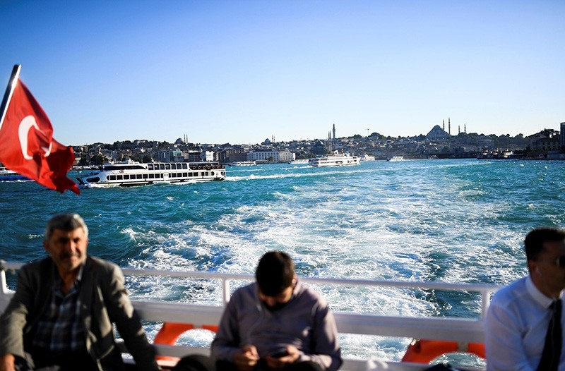 People travel by ferry boat on the Bosporus after it has turned turquoise due to phytoplankton on June 14, 2017, in Istanbul. (AFP Photo)