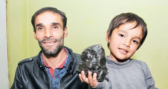 Hasan Beldek poses with his son holding a large meteorite he found in his village Sarıçiçek in this undated photo.