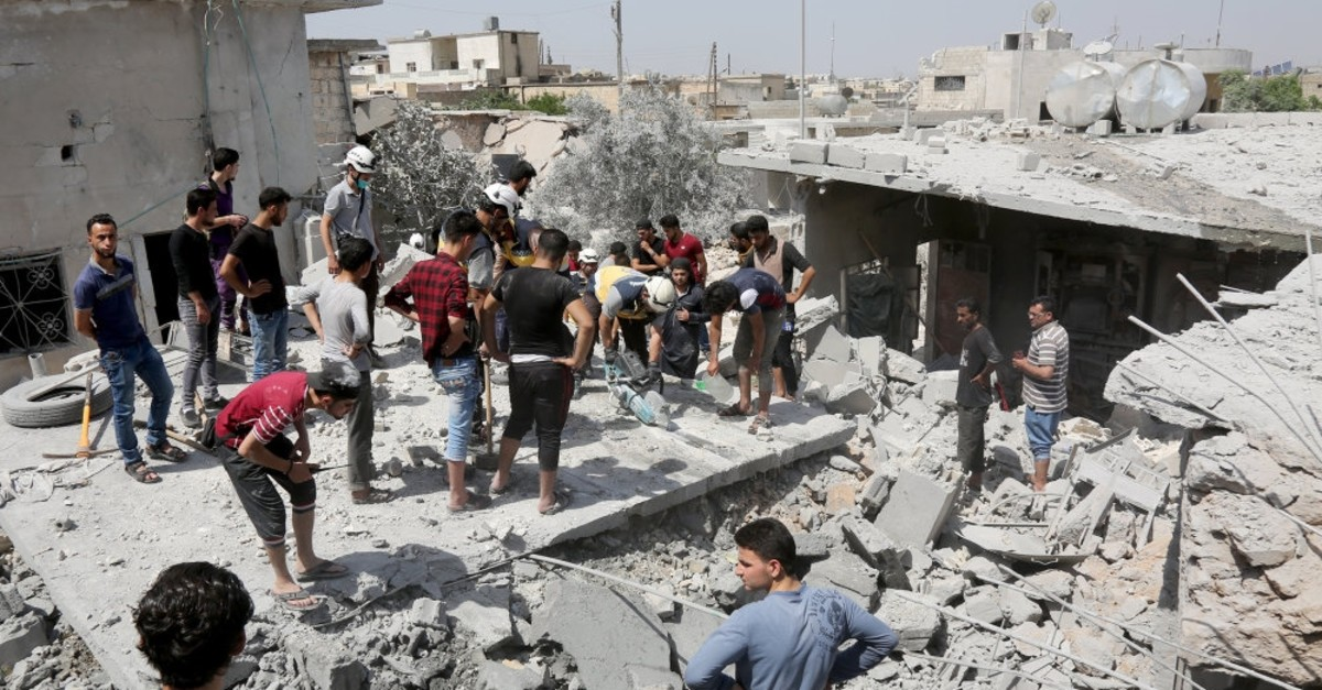 Civil society organizations and rescuers work through the rubble of collapsed buildings destroyed by Syrian regime attacks in Idlib's de-escalation zone, June 11, 2019.