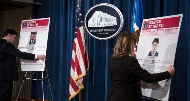 Staff members reveal wanted posters for two of three Russians charged with the 2014 hack of Yahoo before a press conference at the US Department of Justice in Washington, DC.