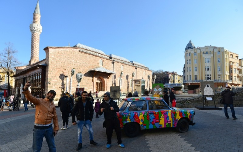 People take selfies with Trabant car exhibited as part of Art Liberte, the first traveling exhibition marking the occasion of the 30 years anniversary of fall of the Berlin wall in the town of Plovdiv, Bulgaria, Saturday, Jan. 12, 2019 (AP Photo)