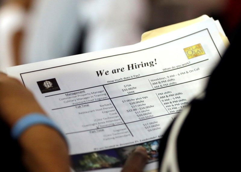 In this Thursday, June 21, 2018 photo, a job applicant looks at job listings for the Riverside Hotel at a job fair hosted by Job News South Florida, in Sunrise, Fla. (AP Photo)