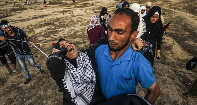 A Palestinian man carries way an injured woman during clashes with Israeli forces near the fence along the border with Israel, near Bureij in the central Gaza Strip on June 28, 2019. (AFP Photo)
