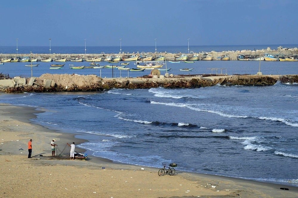 This file photo taken on August 10, 2014 shows Palestinian fishermen picking through their nets on August 10, 2014 on the beach in Gaza City. (AFP Photo)