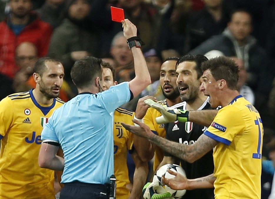Referee Michael Oliver shows a red card to Juventus goalkeeper Gianluigi Buffon during a Champions League quarter final second leg match between Real Madrid and Juventus at the Santiago Bernabeu stadium, Madrid.