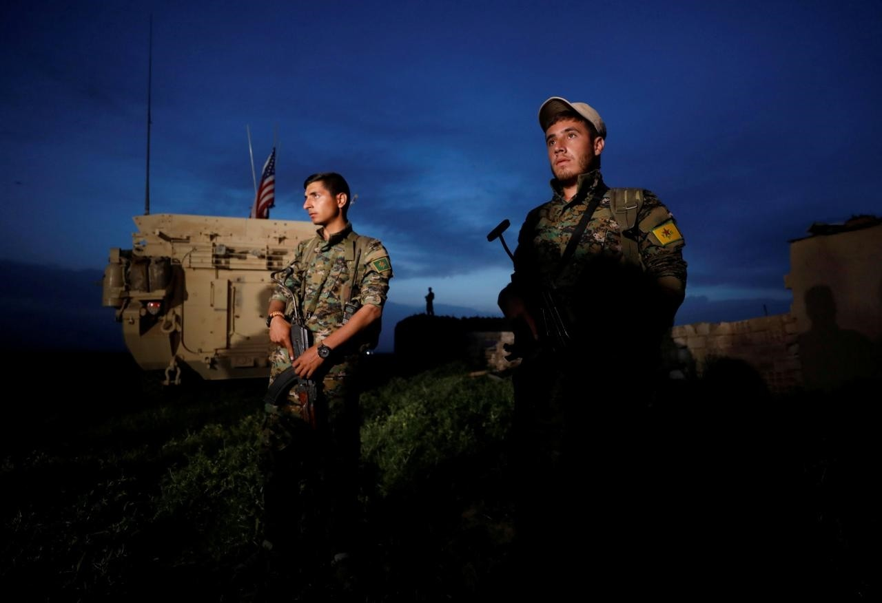 Fighters from the People's Protection Units (YPG) terrorist group stand near a U.S military vehicle in the town of Darbasiya near the Turkish border, Syria April 28, 2017. (Reuters Photo)
