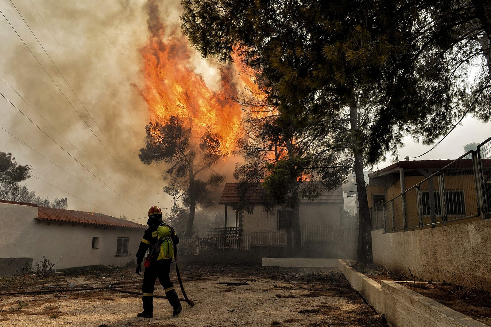 A firefighter tries to extinguish hotspots during a wildfire in Kineta, near Athens, on July 23, 2018.