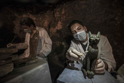 An Egyptian archaeologist cleans a bronze ancient sitting cat statue during a demonstration of a new discovery made by an Egyptian archaeological mission through excavation work carried out since April near the King Userkaf pyramid complex in Saqqara Necropolis, on Nov. 10, 2018. (AFP Photo)