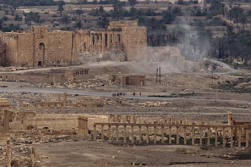 Russian soldiers stand on a road as smoke rises from a controlled land mine detonation by Russian experts inside the ancient town of Palmyra, Syria in the central Homs province. (AP File Photo)
