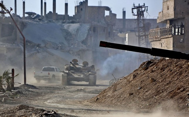 A regime tank rolls in the former opposition-held area of Beit Nayem in the eastern Ghouta region on the outskirts of the capital Damascus on March 6, 2018. (AFP Photo)
