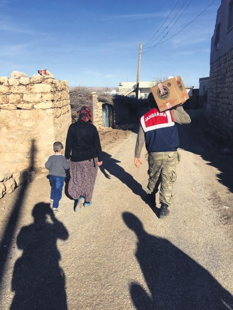 Turkish soldier seen helping a woman carrying food supplies in Nusaybin district of Mardin province Tuesday.