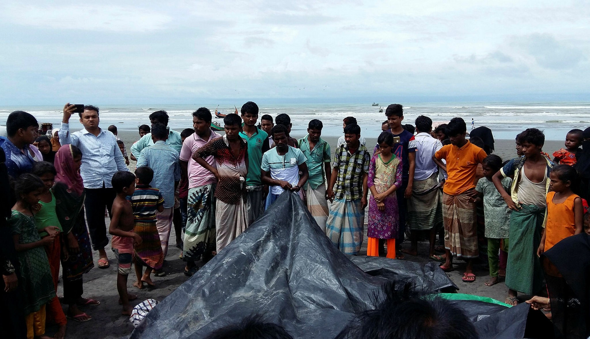 A man covers the bodies of Rohingya women and children who drowned after their boat capsized on the Naf River estuary near Teknaf, Aug. 31.