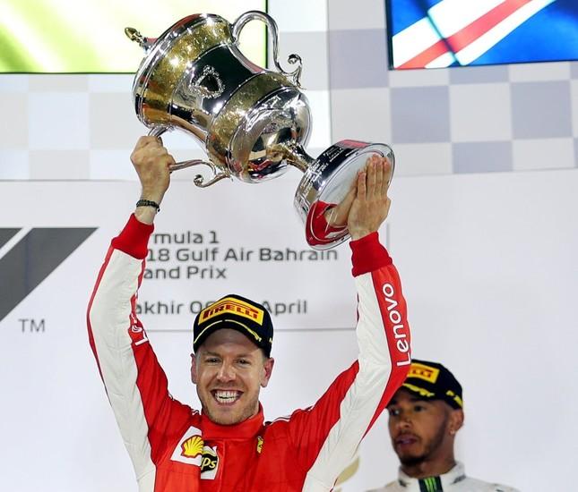 Ferrari's Sebastian Vettel celebrates winning the race with the trophy as Mercedes' Lewis Hamilton looks on.
