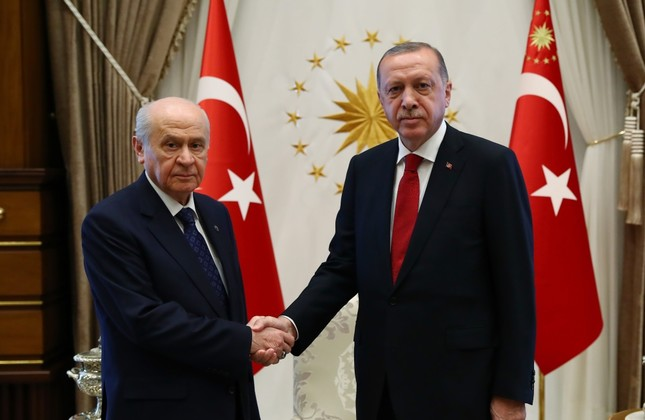 President Recep Tayyip Erdoğan shakes hands with MHP Chairman Devlet Bahçeli (L).