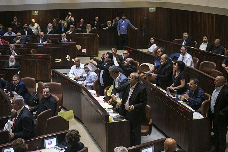 Arab lawmakers stand up in protest during a Knesset session in Jerusalem on July 19, 2018. (AP Photo)