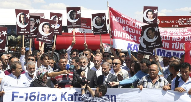 Protesters hold photos of people killed outside Akıncı Air Base on July 15, 2016, while AK Party lawmaker Taner Yıldız speaks in front of the courthouse where the coup suspects are on trial in Ankara.
