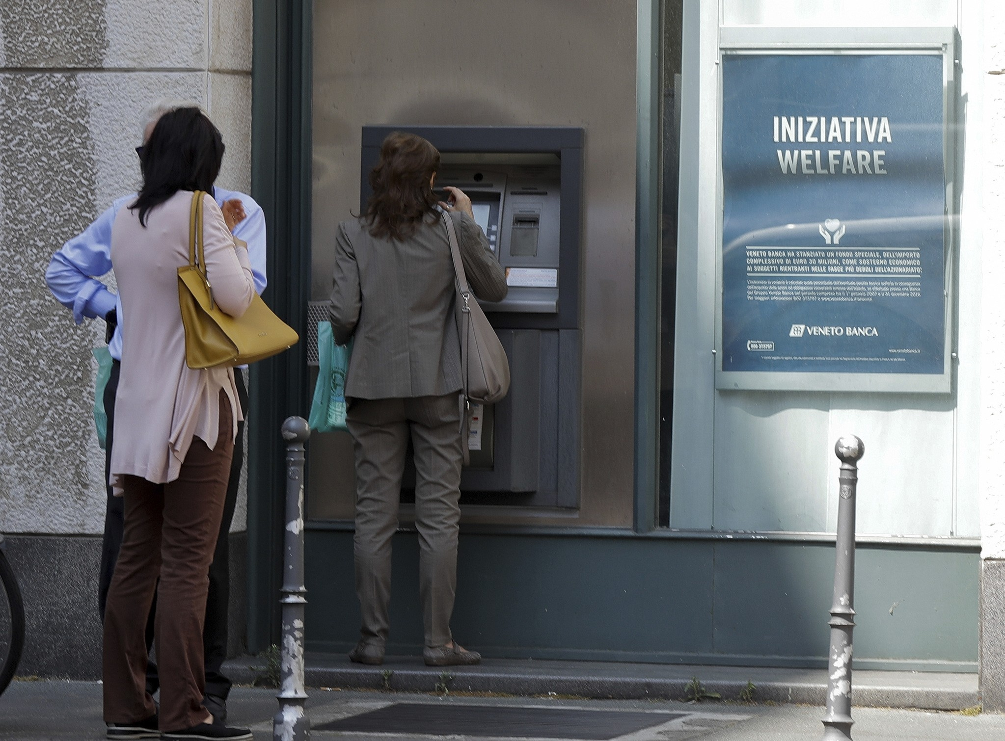 People line up at a cash machine of a Veneto Banca branch in Milan, Italy, Monday, June 26, 2017. (AP Photo)