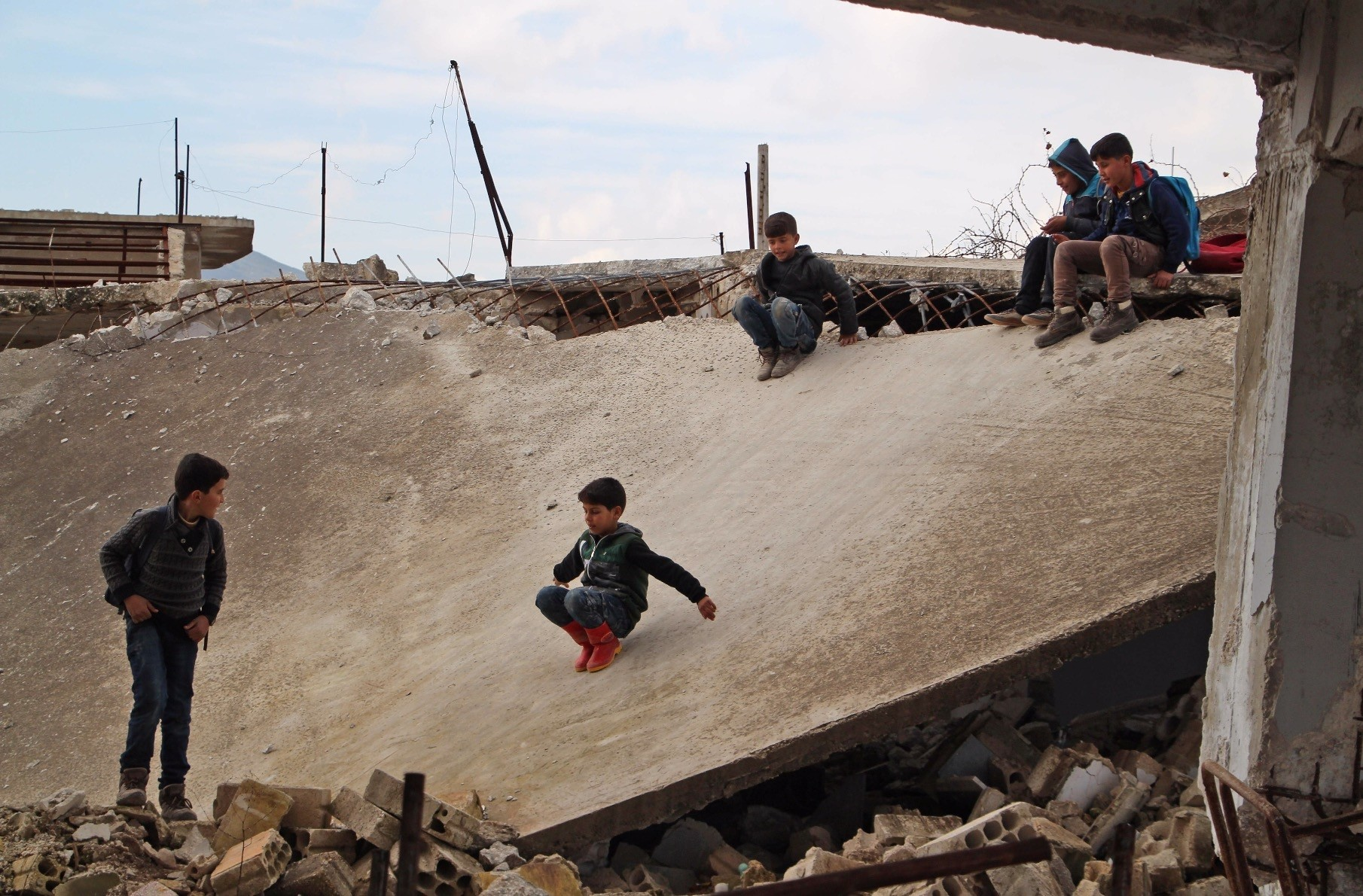 Syrian children slide on the collapsed roof of a school which was bombarded in the district of Jisr  al-Shughur, Idlib, Jan. 30, 2019.