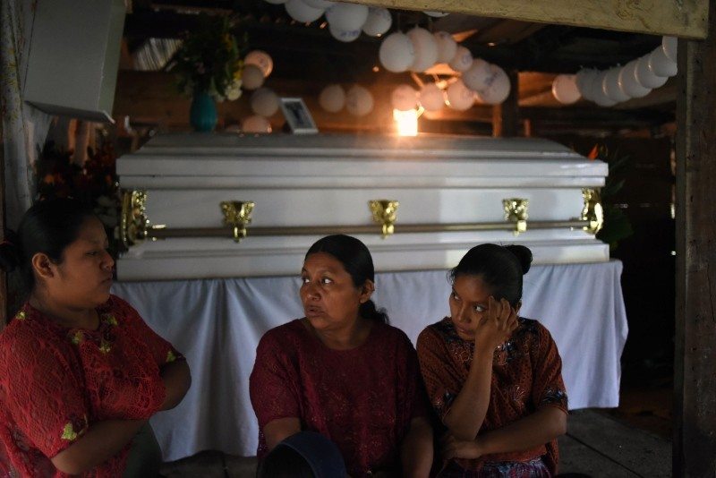 Local indigenous women sit next to the coffin of 7-year old Jakelin Amei Rosmery Caal, who died in a Texas hospital two days after being taken into custody by border patrol agents, Raxruha Village, Guatemala City, Dec. 24, 2018. (AFP Photo)