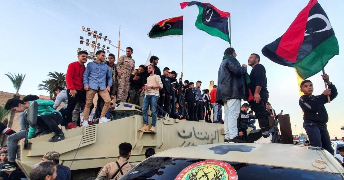 People stand with Libyan national flags above armoured military vehicles of forces loyal to the UN-recognised Tripoli-based ,Government of National Accord, (GNA) during a celebration in the capital's Martyrs' Square, Jan. 31, 2020. (AFP)