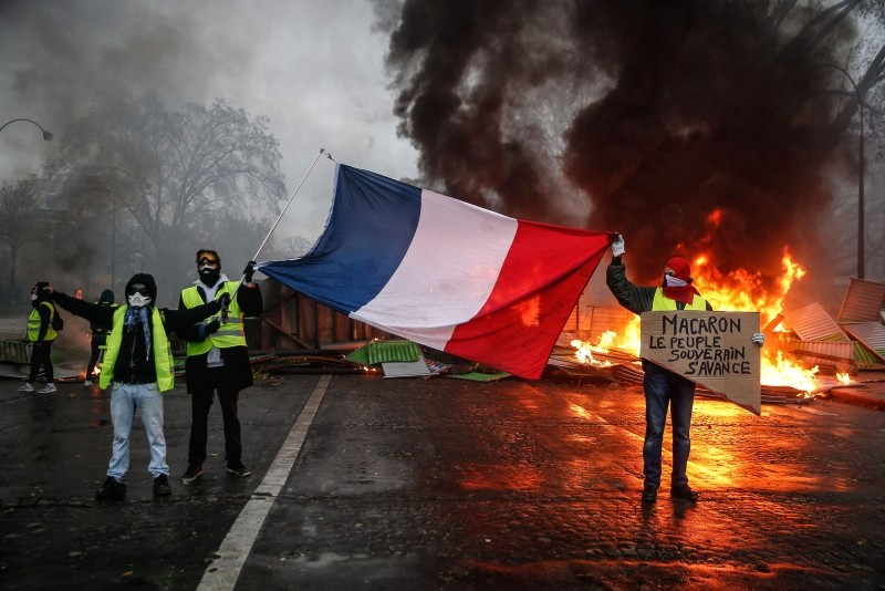 Protesters hold a French flag near a burning barricade during a protest of Yellow vests (Gilets jaunes) against rising oil prices and living costs, on December 1, 2018 in Paris. (AFP Photo)