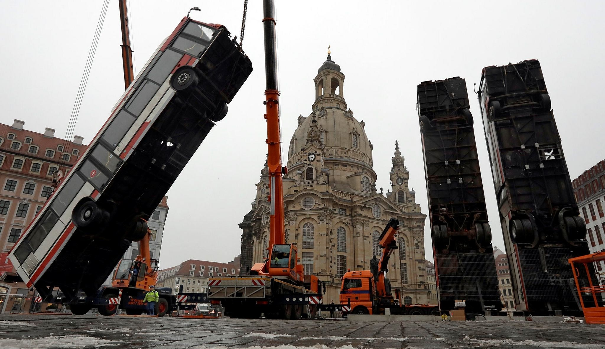 Three buses are positioned close to the 'Frauenkirche' church in Dresden, Germany, Monday, Feb. 6, 2017. Syrian artist Manaf Halbouni placed the three buses upright to evoke the suffering of civilians in the Syrian city of Aleppo. (AP Photo)