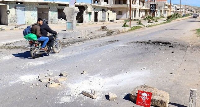 Men ride a motorbike past a hazard sign at a site hit by an airstrike on Tuesday in the town of Khan Sheikhoun in opposition-held Idlib (Reuters Photo)